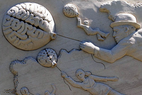 relief sculpture of people floating on brain balloons