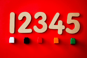 numbers one, two, three, four, and five on a red background sitting above legos