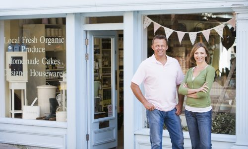 couple standing in front of small business